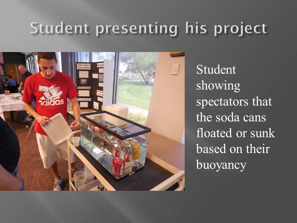 Student showing spectators that the soda cans floated or sunk based on their buoyancy