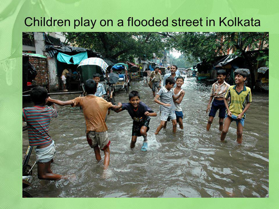 Children play on a flooded street in Kolkata
