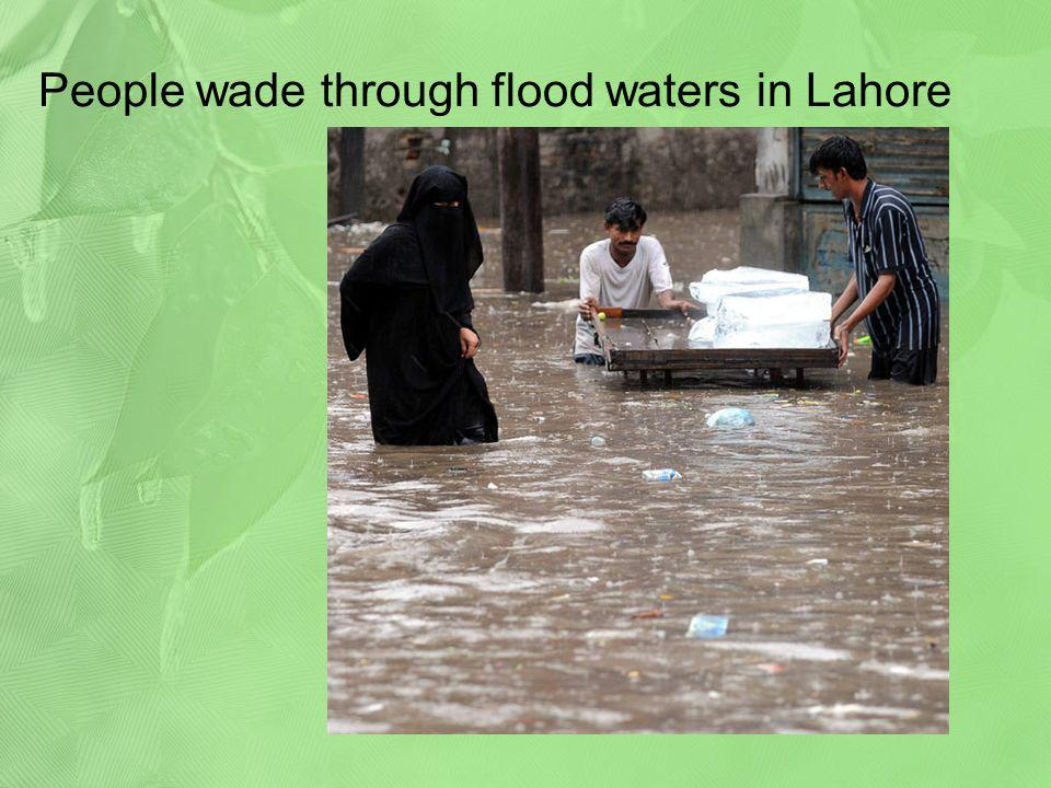 People wade through flood waters in Lahore