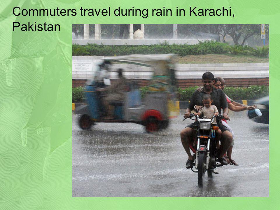 Commuters travel during rain in Karachi, Pakistan