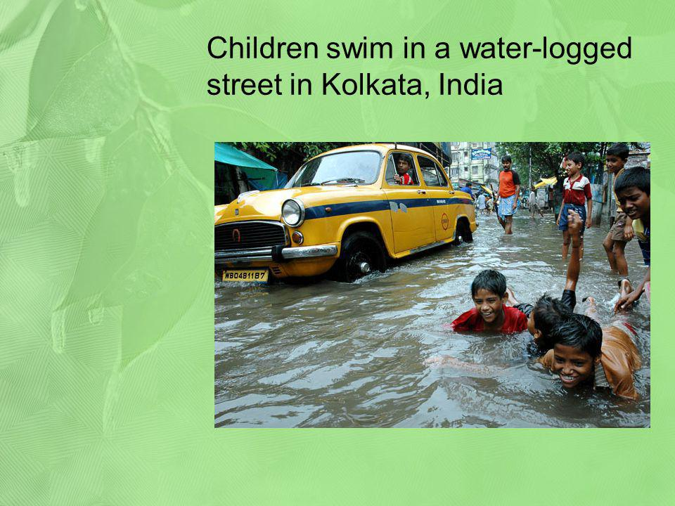 Children swim in a water-logged street in Kolkata, India