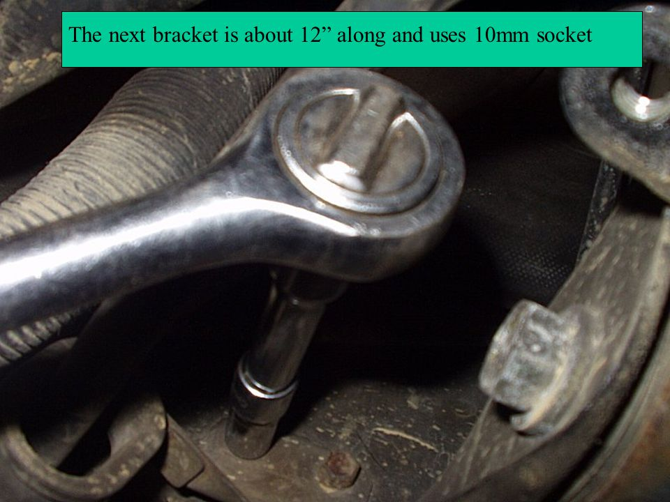The next bracket is a clamp through which the cable runs, the nut is 10mm, undo the nut and the clamp falls out