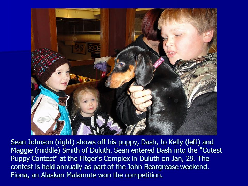 Sean Johnson (right) shows off his puppy, Dash, to Kelly (left) and Maggie (middle) Smith of Duluth. Sean entered Dash into the
