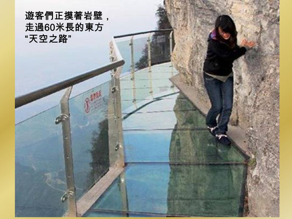Dont look down: A brave tourist walks along the glass path that was built on the side of a cliff, 4,700ft above sea level, on Tianmen Mountain in Zhan