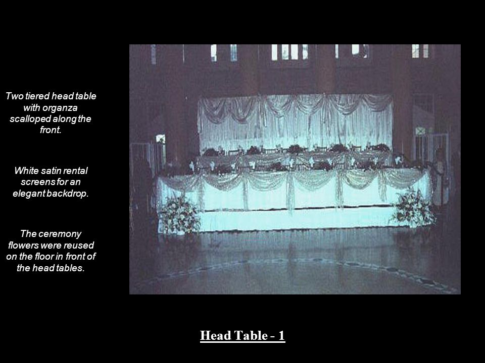 Two tiered head table with organza scalloped along the front. White satin rental screens for an elegant backdrop. The ceremony flowers were reused on