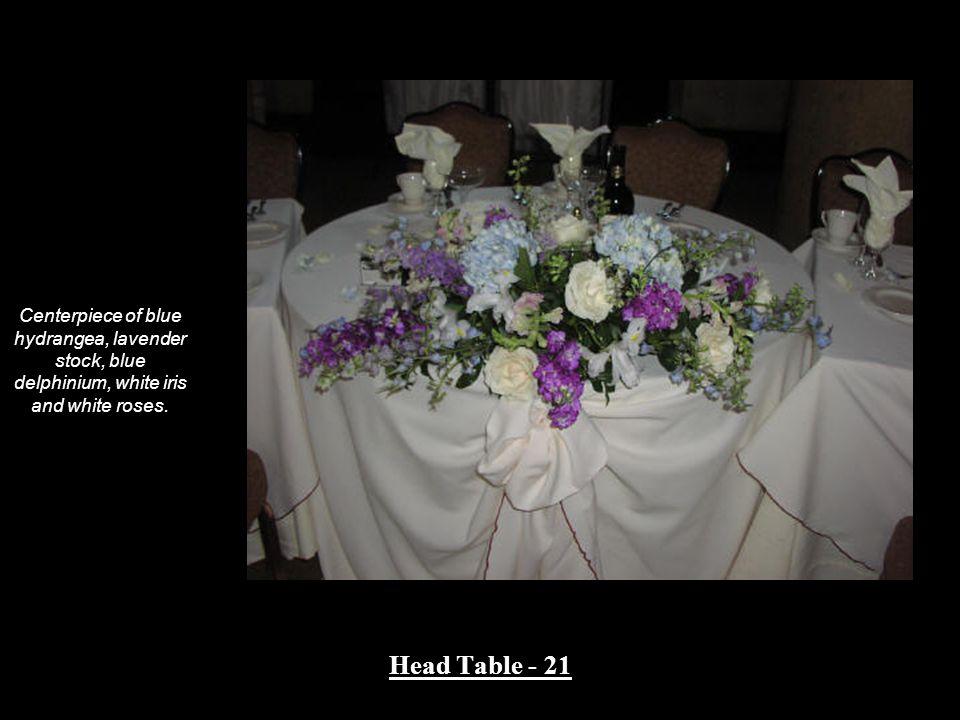 Centerpiece of blue hydrangea, lavender stock, blue delphinium, white iris and white roses. Head Table - 21