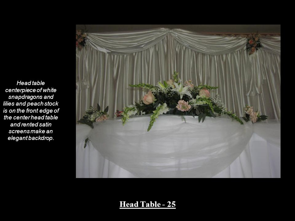 Head table centerpiece of white snapdragons and lilies and peach stock is on the front edge of the center head table and rented satin screens make an