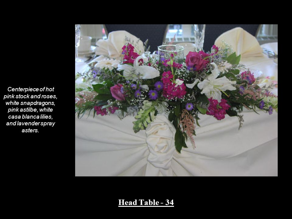 Centerpiece of hot pink stock and roses, white snapdragons, pink astilbe, white casa blanca lilies, and lavender spray asters. Head Table - 34