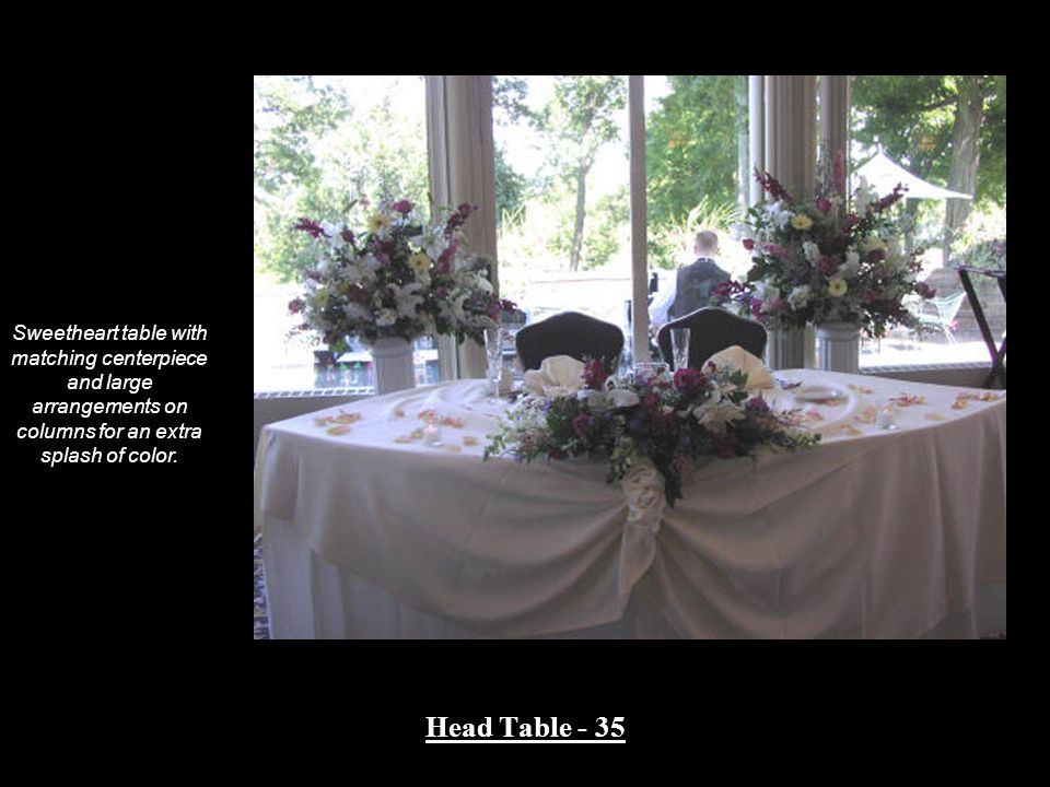 Head Table - 35 Sweetheart table with matching centerpiece and large arrangements on columns for an extra splash of color.