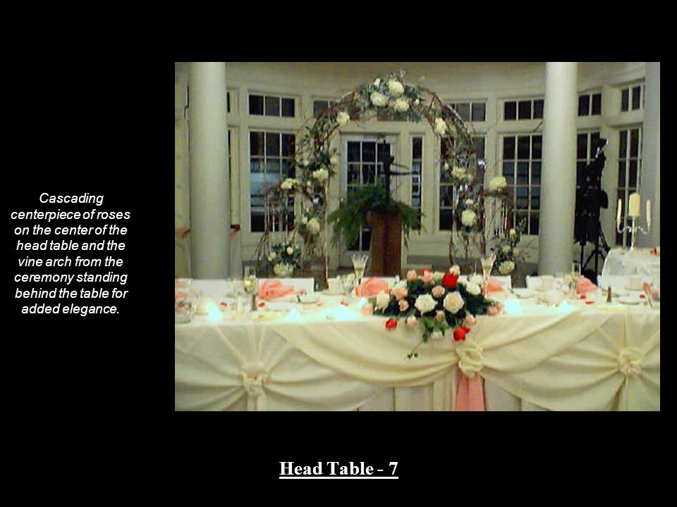 Cascading centerpiece of roses on the center of the head table and the vine arch from the ceremony standing behind the table for added elegance. Head