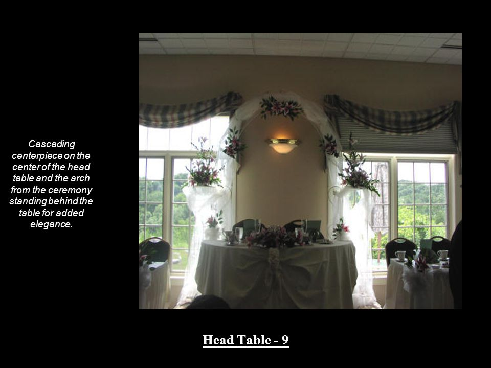 Cascading centerpiece on the center of the head table and the arch from the ceremony standing behind the table for added elegance. Head Table - 9