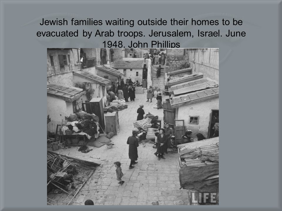 Jewish families waiting outside their homes to be evacuated by Arab troops.