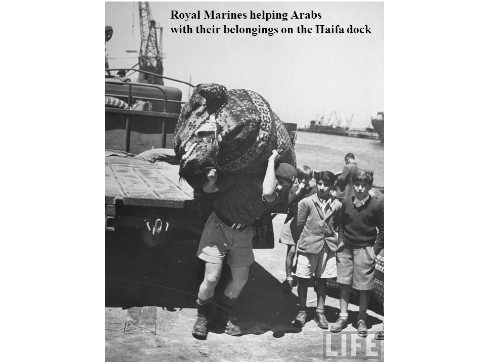 Royal Marines helping Arabs with their belongings on the Haifa dock
