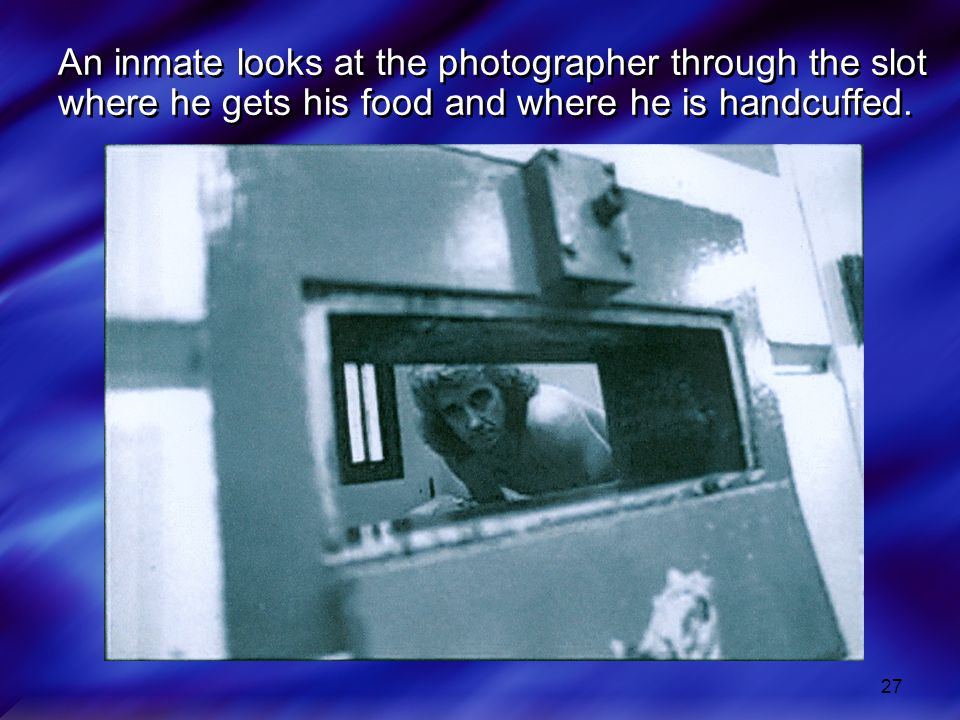 27 An inmate looks at the photographer through the slot where he gets his food and where he is handcuffed.