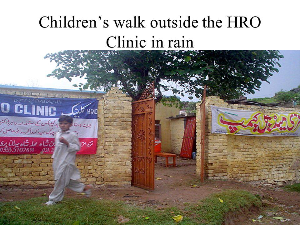 Childrens walk outside the HRO Clinic in rain