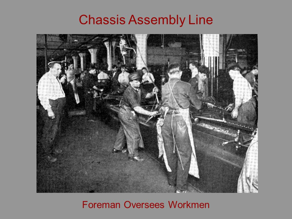 Chassis Assembly Line Foreman Oversees Workmen