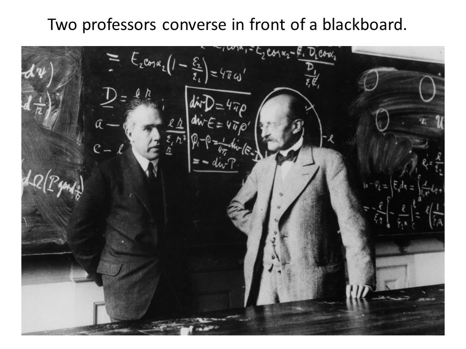 Two professors converse in front of a blackboard.