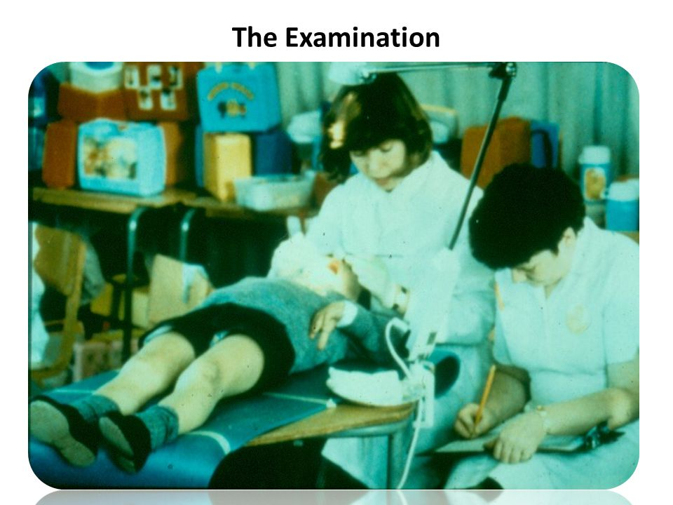 Dentist seated behind child Child lying supine on table covered with soft mat or in reclined chair Recorder seated next to dentist Dentist can clearly see chart