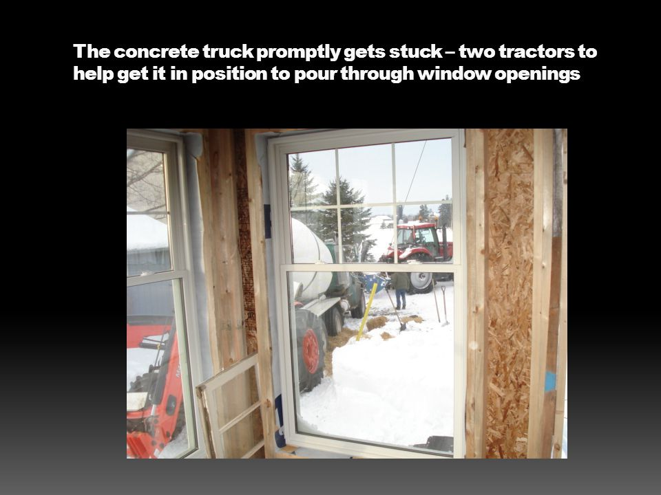 The concrete truck promptly gets stuck – two tractors to help get it in position to pour through window openings