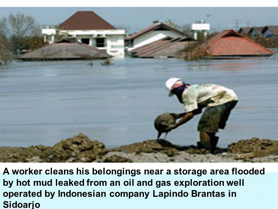 A worker cleans his belongings near a storage area flooded by hot mud leaked from an oil and gas exploration well operated by Indonesian company Lapindo Brantas in Sidoarjo