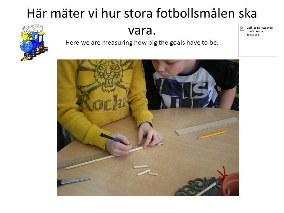 Här mäter vi hur stora fotbollsmålen ska vara. Here we are measuring how big the goals have to be.