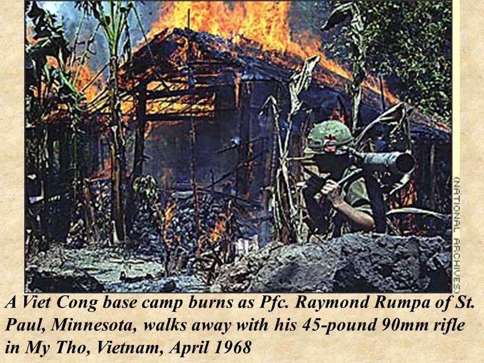 A Viet Cong base camp burns as Pfc. Raymond Rumpa of St.