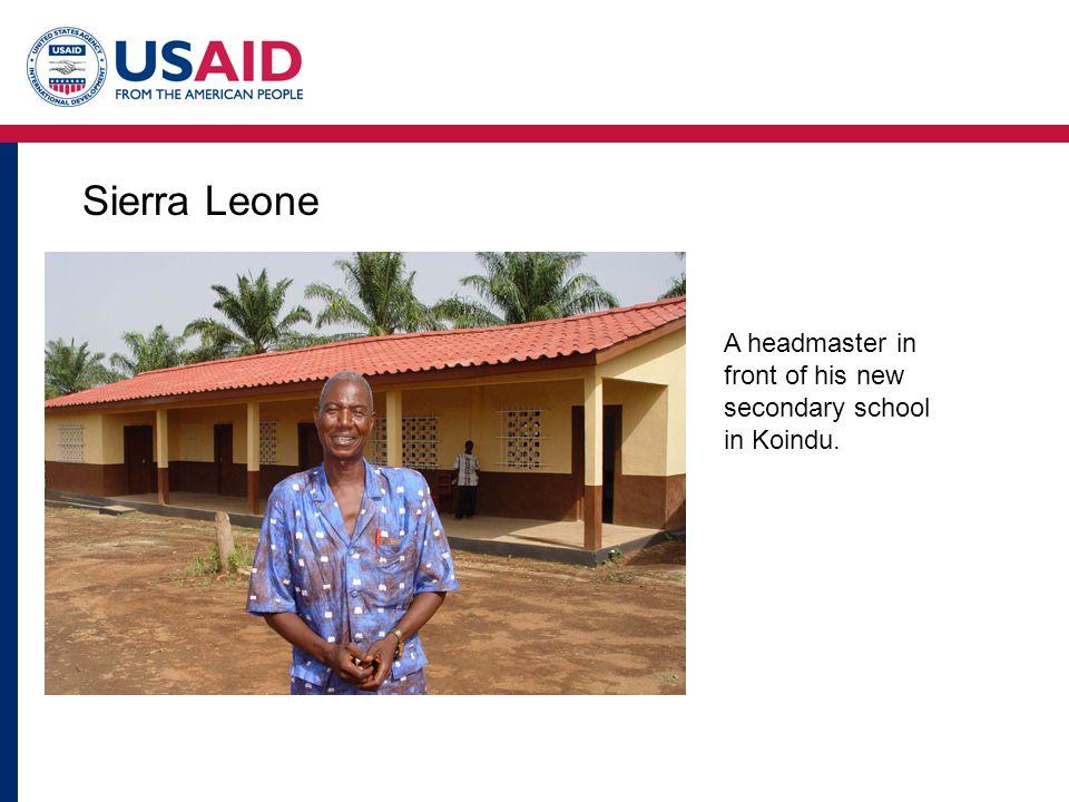 Sierra Leone A headmaster in front of his new secondary school in Koindu.