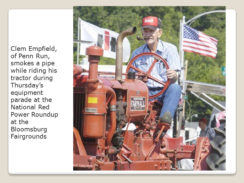 Clem Empfield, of Penn Run, smokes a pipe while riding his tractor during Thursday's equipment parade at the National Red Power Roundup at the Bloomsb