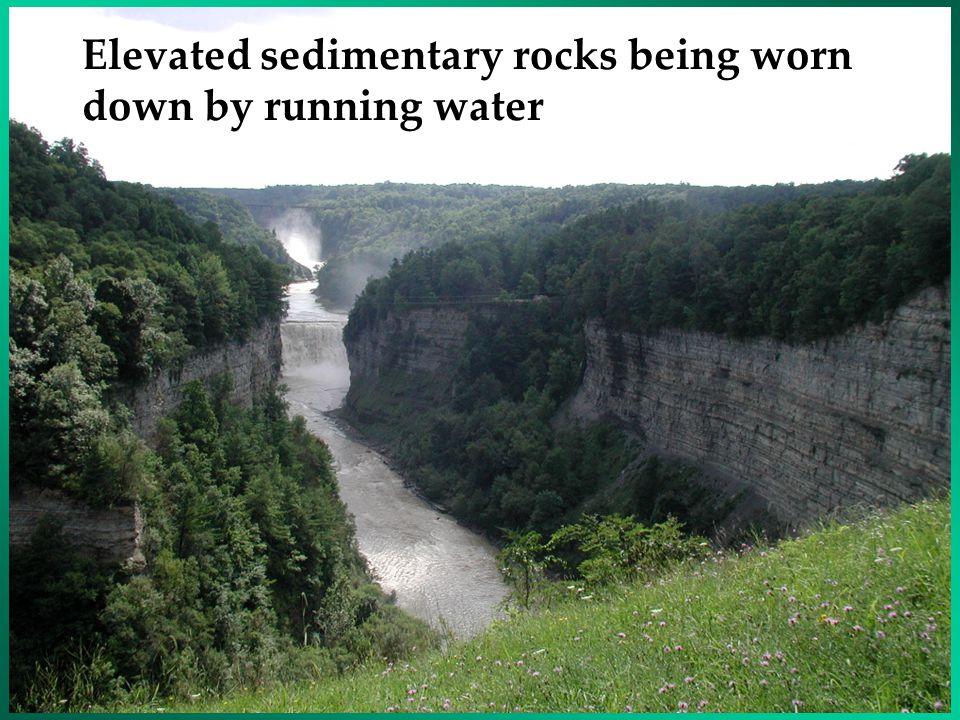 Elevated sedimentary rocks being worn down by running water