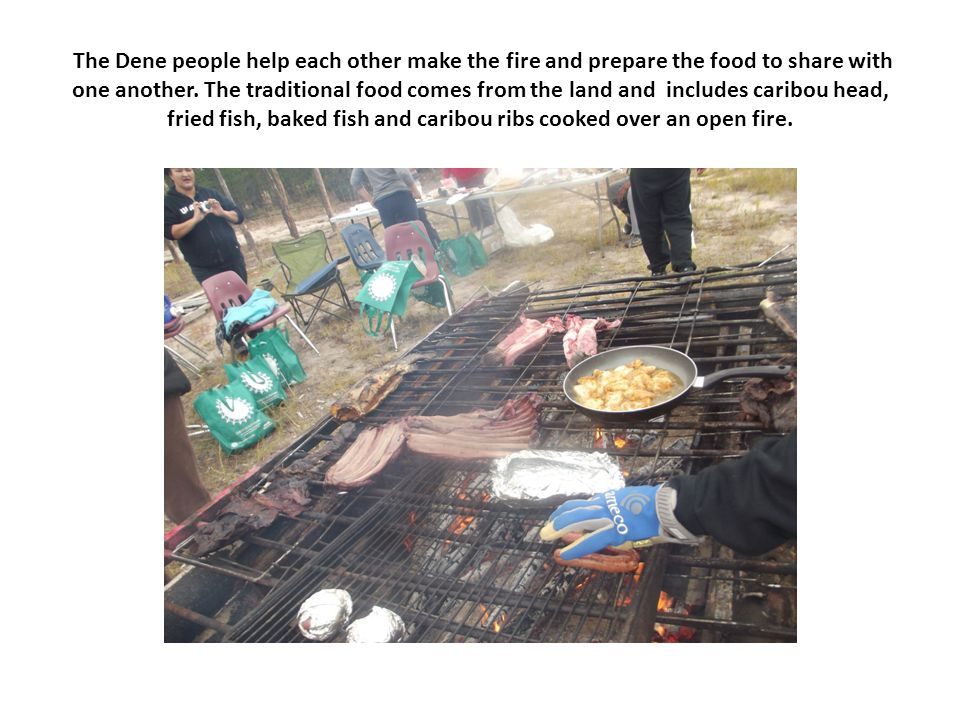 The Dene people help each other make the fire and prepare the food to share with one another. The traditional food comes from the land and includes ca