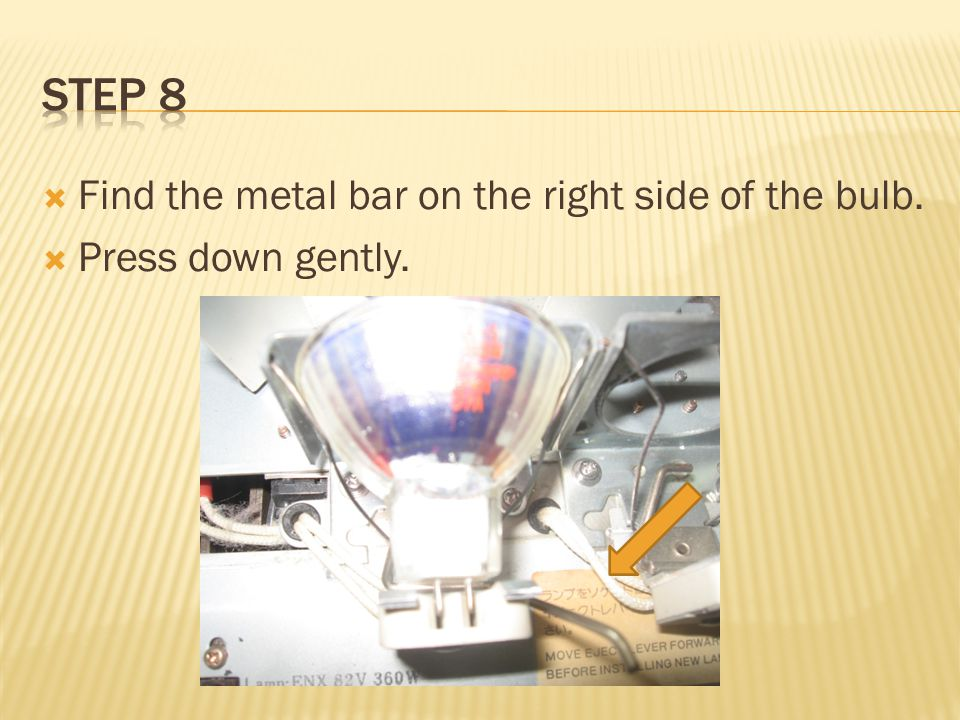  Find the metal bar on the right side of the bulb.  Press down gently.