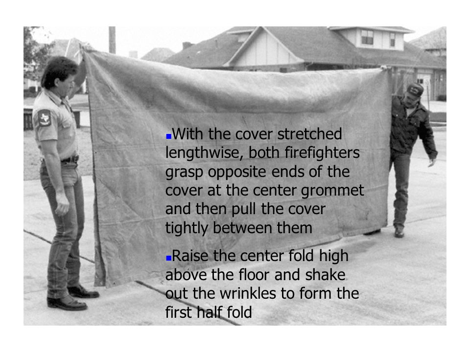 With the cover stretched lengthwise, both firefighters grasp opposite ends of the cover at the center grommet and then pull the cover tightly between