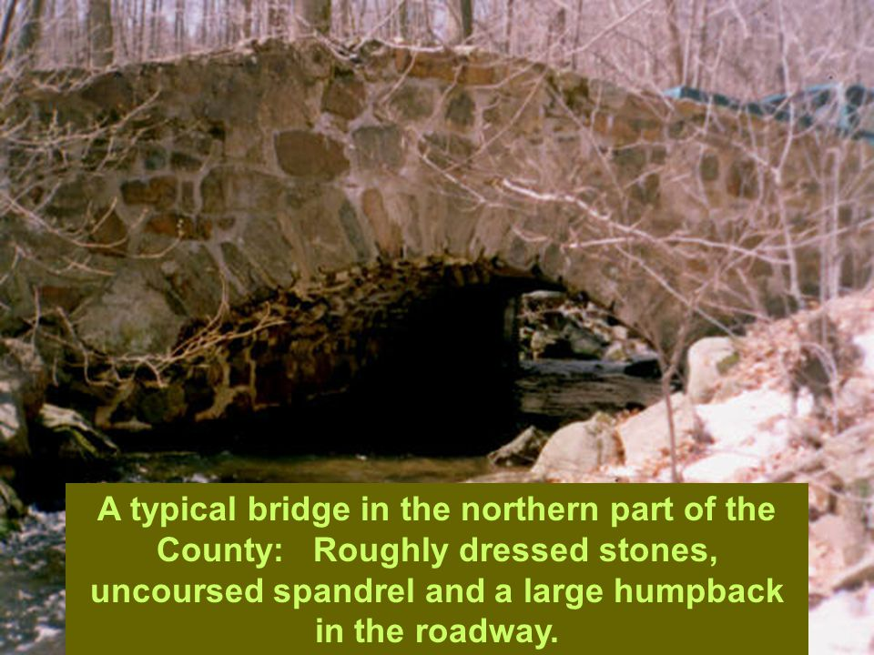 A typical bridge in the northern part of the County: Roughly dressed stones, uncoursed spandrel and a large humpback in the roadway.