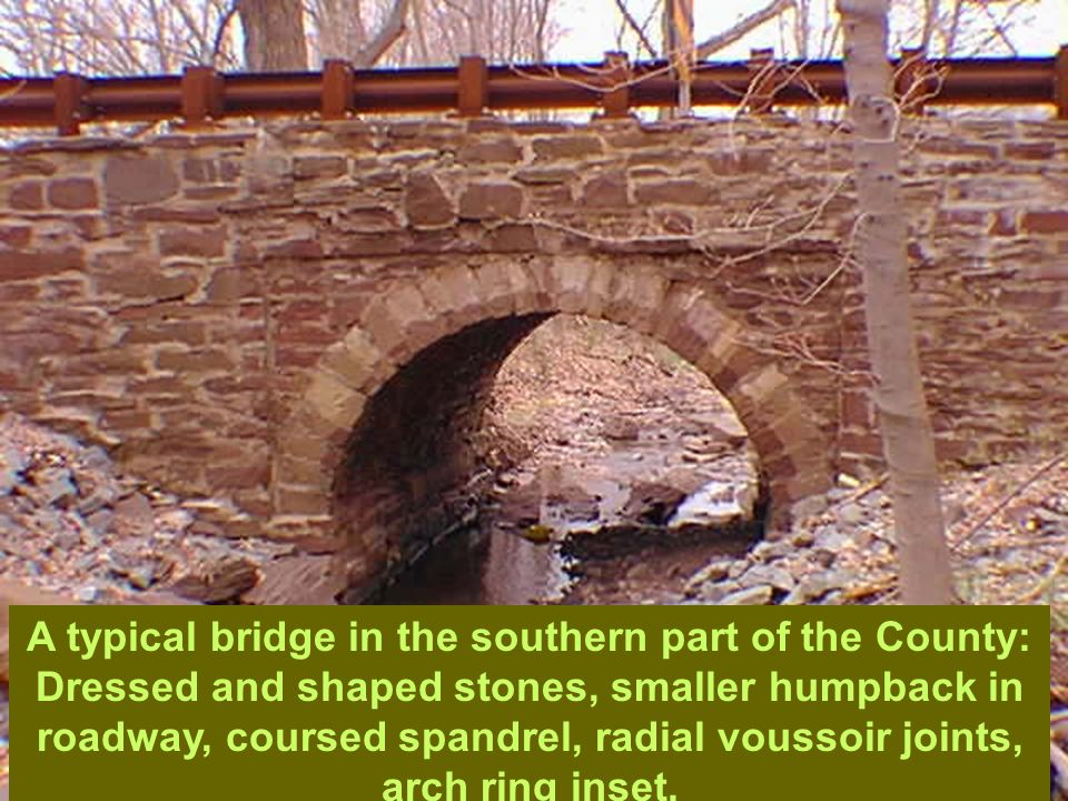 W-115 A typical bridge in the southern part of the County: Dressed and shaped stones, smaller humpback in roadway, coursed spandrel, radial voussoir j