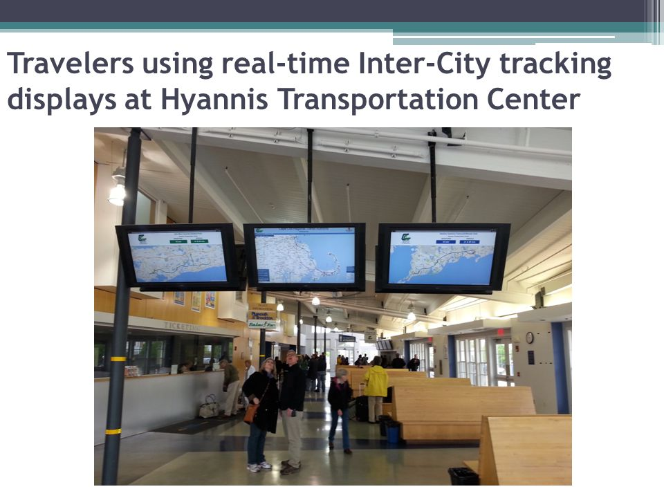 Travelers using real-time Inter-City tracking displays at Hyannis Transportation Center