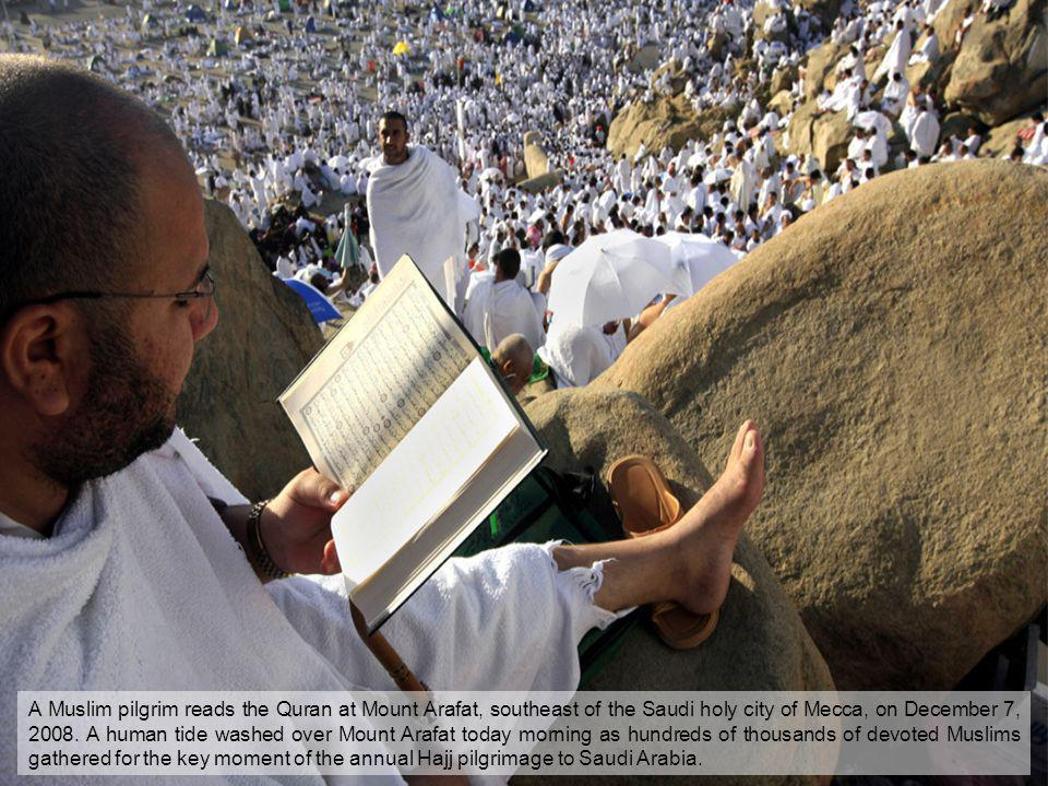 A Muslim pilgrim reads the Quran at Mount Arafat, southeast of the Saudi holy city of Mecca, on December 7, 2008. A human tide washed over Mount Arafa