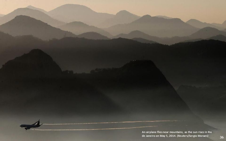 An airplane flies near mountains, as the sun rises in Rio de Janeiro on May 5, 2014.
