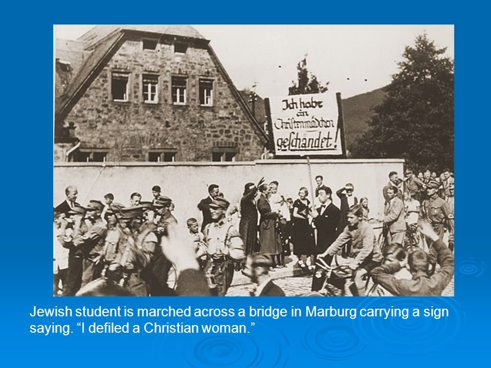 "Jewish student is marched across a bridge in Marburg carrying a sign saying. ""I defiled a Christian woman."""