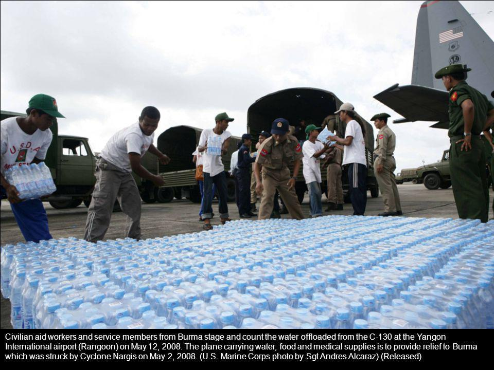 Civilian aid workers and service members from Burma stage and count the water offloaded from the C-130 at the Yangon International airport (Rangoon) o