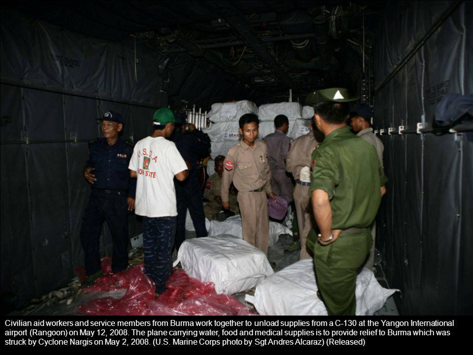 Civilian aid workers and service members from Burma work together to unload supplies from a C-130 at the Yangon International airport (Rangoon) on May