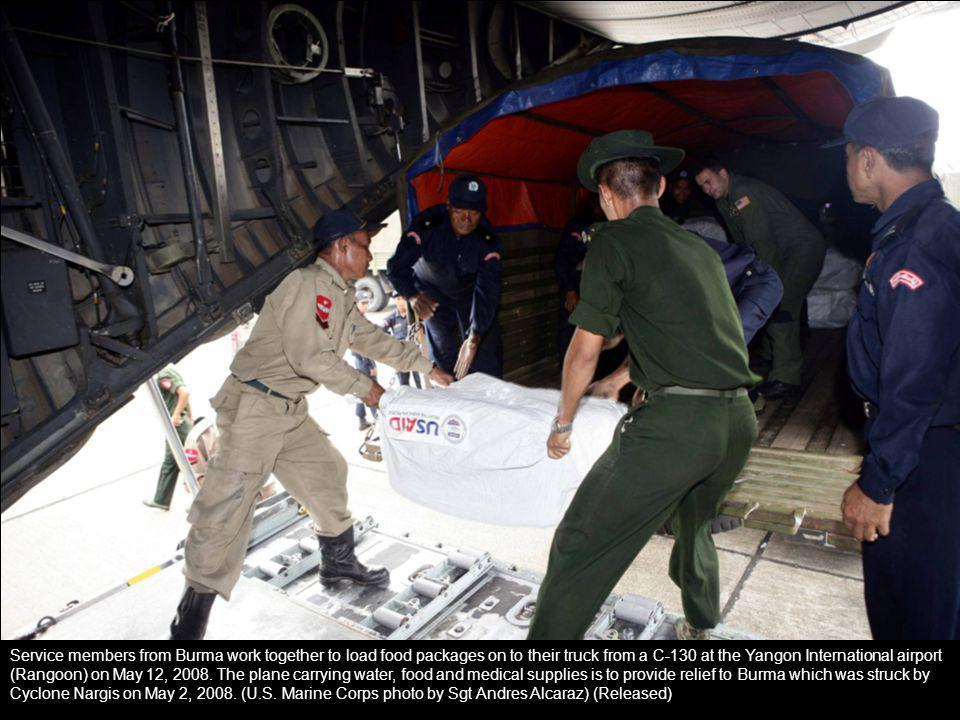 Service members from Burma work together to load food packages on to their truck from a C-130 at the Yangon International airport (Rangoon) on May 12,