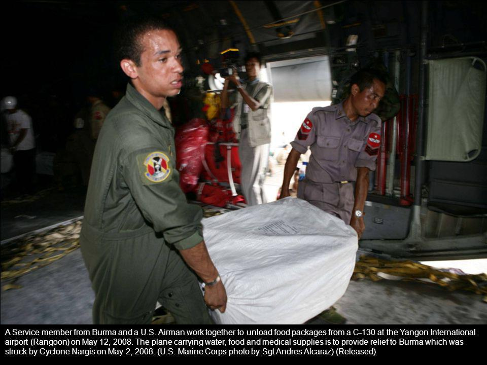 A Service member from Burma and a U.S. Airman work together to unload food packages from a C-130 at the Yangon International airport (Rangoon) on May