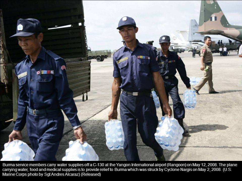 Burma service members carry water supplies off a C-130 at the Yangon International airport (Rangoon) on May 12, 2008. The plane carrying water, food a