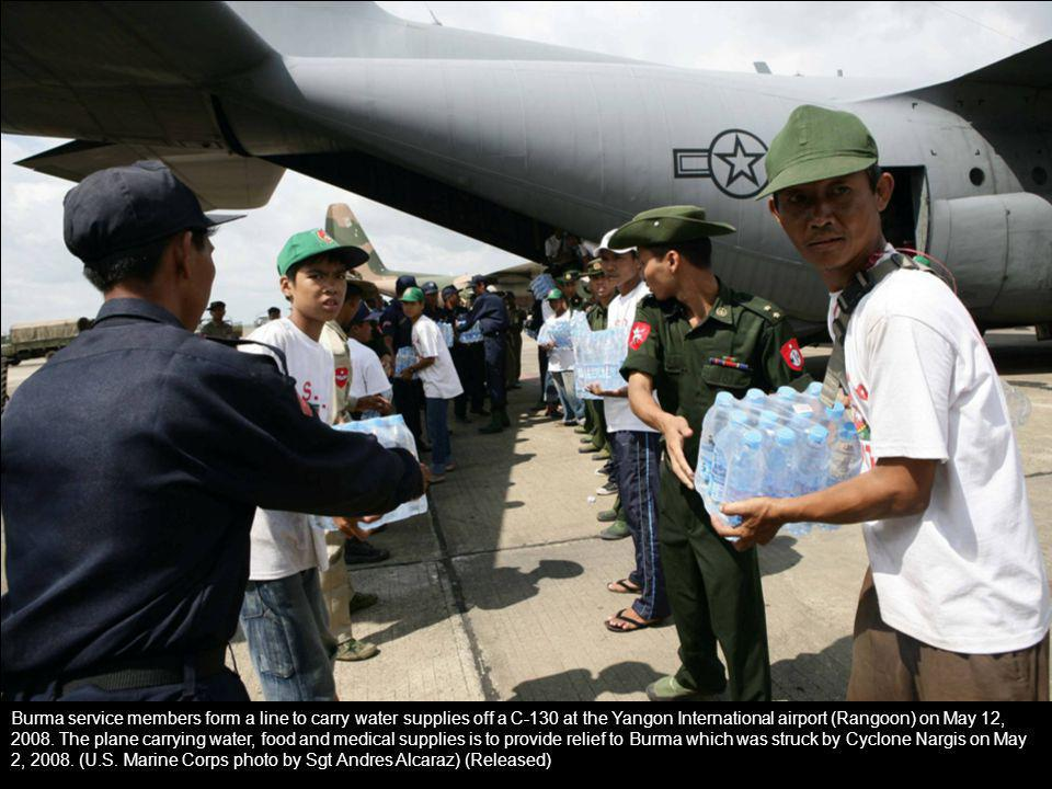 Burma service members form a line to carry water supplies off a C-130 at the Yangon International airport (Rangoon) on May 12, 2008. The plane carryin