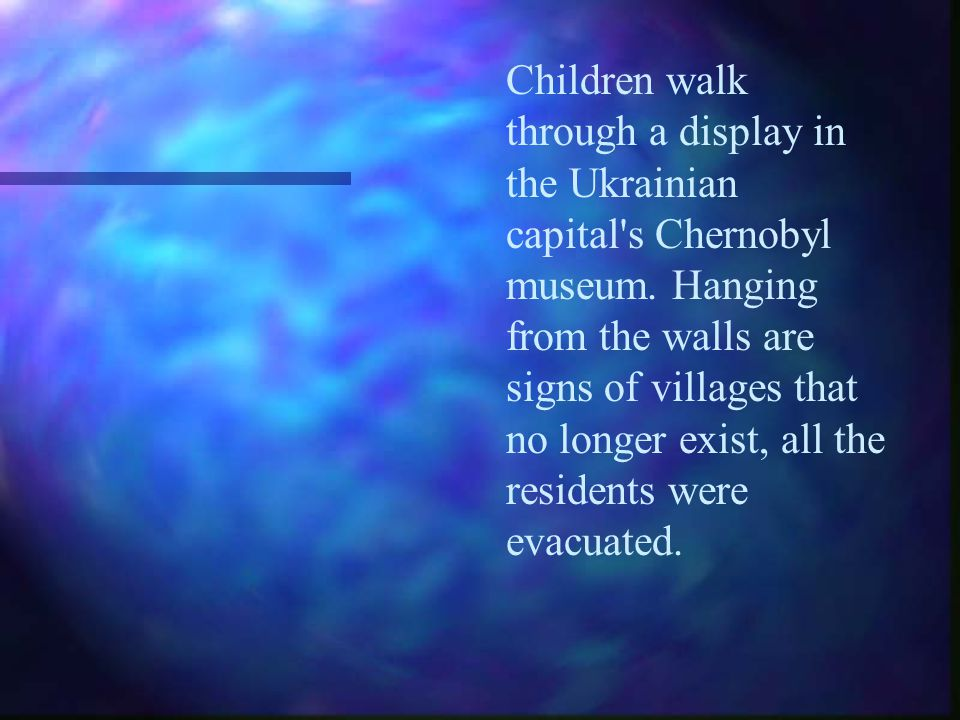 Children walk through a display in the Ukrainian capital's Chernobyl museum. Hanging from the walls are signs of villages that no longer exist, all th