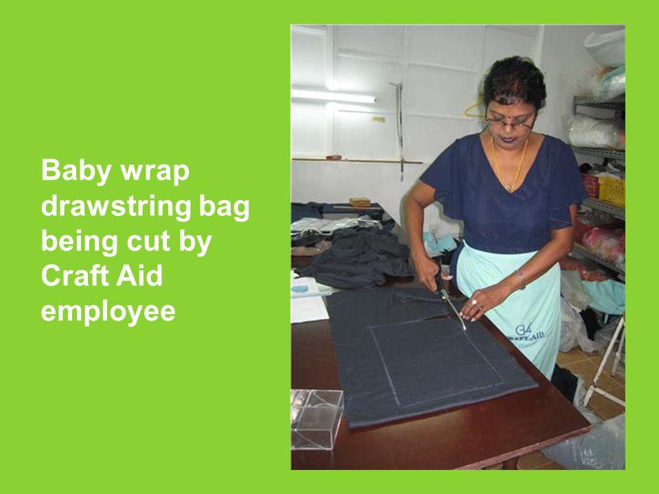 Baby wrap drawstring bag being cut by Craft Aid employee