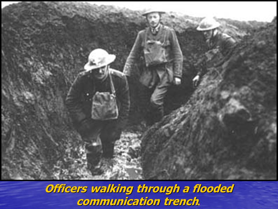 Officers walking through a flooded communication trench communication trench.