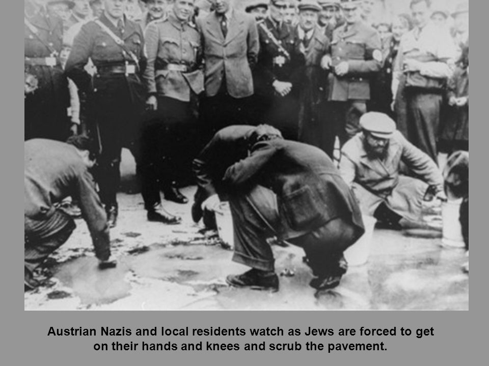 Austrian Nazis and local residents watch as Jews are forced to get on their hands and knees and scrub the pavement.