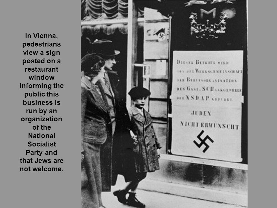 In Vienna, pedestrians view a sign posted on a restaurant window informing the public this business is run by an organization of the National Socialist Party and that Jews are not welcome.