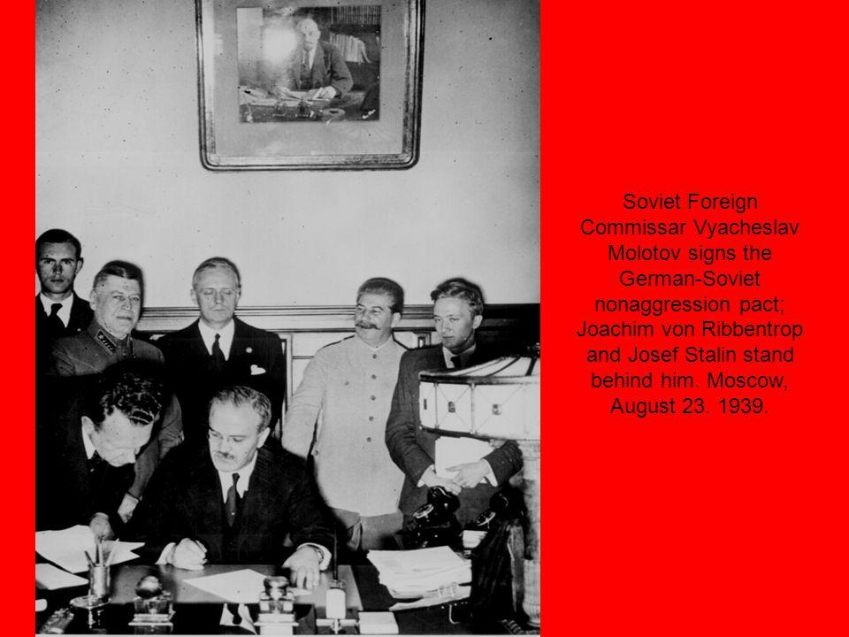 Soviet Foreign Commissar Vyacheslav Molotov signs the German-Soviet nonaggression pact; Joachim von Ribbentrop and Josef Stalin stand behind him.